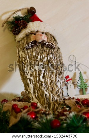 Christmas decoration of Santa's head on a wooden log with small colorful decorations around it over a white background