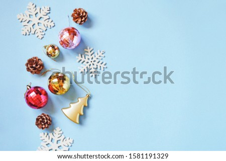 Christmas decoration on a light blue background. Red, yellow, pink balls, pine cones and snowflakes. Festive New Year border, mockup, banner. Flat lay photo, free space for text #1581191329