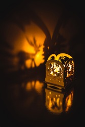 Christmas decoration on a shiny surface. A small wooden lantern with a candle inside casting a shadow on a golden background.