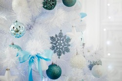 christmas decoration on a white christmastree with lights and bokeh in the background