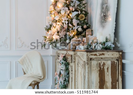 Christmas decoration on ancient vintage old commode chest of drawers. Hand made craft gifts, candels and a tree at background. Selective focus