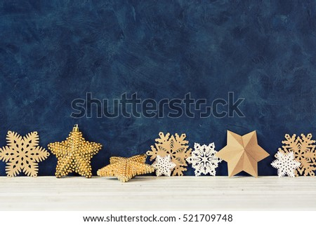 Christmas decoration on the blue vintage background. Paper snowflakes and gold stars. New year greeting card template. Holiday mock up. Scandinavian style.