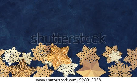 Christmas decoration  on the blue vintage background. Paper snowflakes and golden stars. New year greeting card template. Holiday mock up. Scandinavian style.