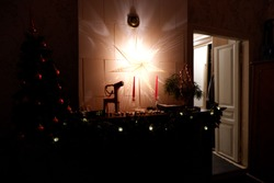Christmas decoration on the fireplace in house. Lamp in the evening and Yule goat