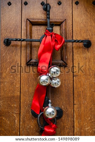 Christmas decoration on the wooden door. Red ribbon and four silver balls with street reflection.