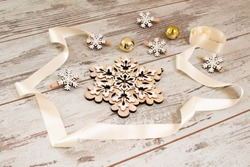 Christmas decoration on white wooden floor with silk ribbon, wooden snowflakes and jingle bells