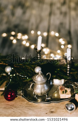Christmas decoration on wooden table. Candles, Christmas tree branch with toys and silver set on blurred lights background. Top view