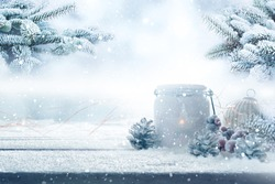 Christmas decoration on wooden table with fir branchs in a snowy garden. Winter background for christmas and advent concepts with space for text.