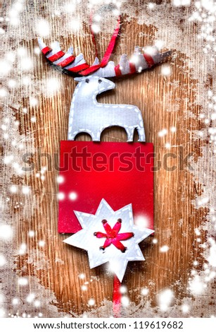 Christmas decoration over grunge background/vintage paper christmas decoration with a sign and red ribbon/Christmas card with a snow texture and wooden  background