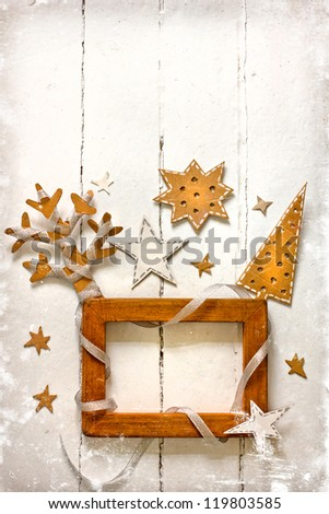 Christmas decoration over white,winter background with the star/vintage paper christmas decoration with a wooden frame