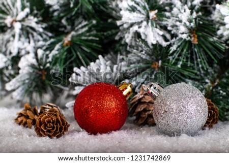 Christmas decoration red and silver balls in a tree with tinsel and pinecone in snow