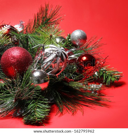 christmas decoration red and silver balls on christmas tree branch over red background holiday - Red Silver Christmas Decorations
