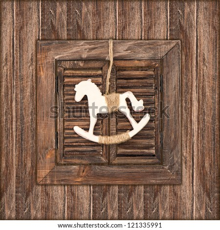christmas decoration rocking horse over wooden window background