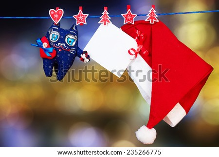 Christmas decoration santa hat and a cat toy and empty sheet of paper with a red ribbon hanging on rope over  blurred lights background #235266775