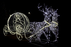 Christmas decoration silver glowing shiny white carriage an deer isolated on black background