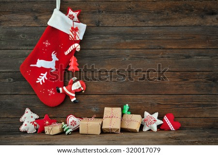 Christmas decoration stocking and toys hanging over rustic wooden background - Shutterstock ID 320017079