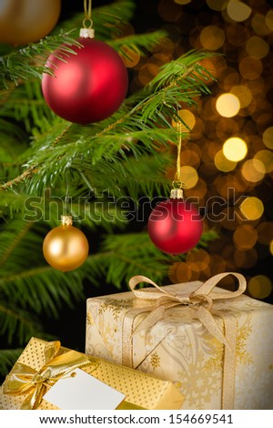 Christmas decoration tree, baubles and gifts on shining lights background