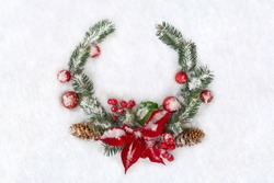 Christmas decoration. Twigs christmas tree, flowers of red poinsettia, brown natural spruce cones, ball, red berries on snow with space for text. Top view, flat lay