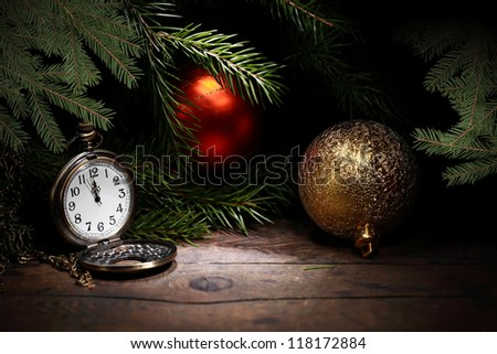 Christmas decoration. Vintage pocket watch on old wooden surface near fir twigs