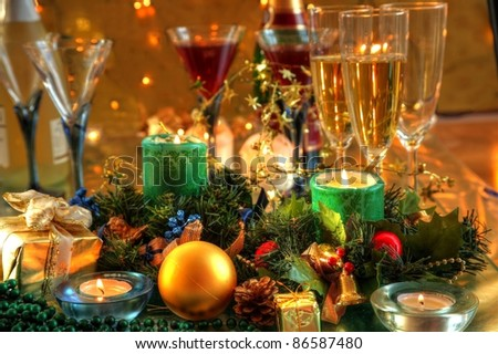 Christmas decoration with baubles,gift,candle lights,green twig,glasses of wine,glasses on background with twinkle lights.