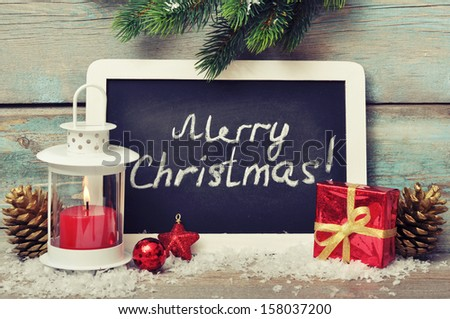 Christmas  decoration with candle in lantern and framed blackboard on wooden background