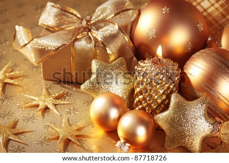 Christmas decoration with candle on golden background