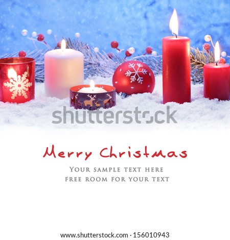 Christmas decoration with candles and ball on snow.