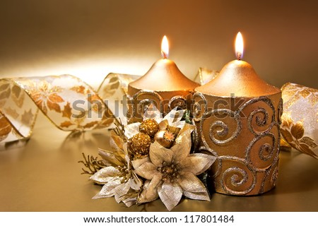 Christmas decoration with candles and ribbon over golden background