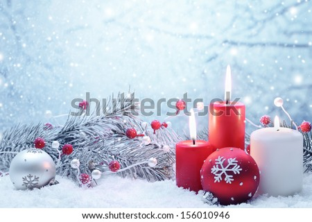 Christmas decoration with candles fir branch and balls on snow
