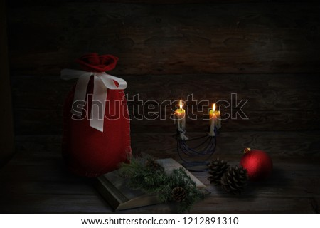 Christmas decoration with 2 Christmas candles, book, pine cones, red ball and Santa sack. Low-key lighting. Wooden background #1212891310