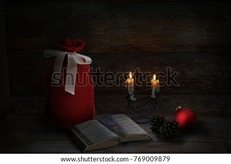 Christmas decoration with 2 Christmas candles, book, pine cones, red ball and Santa sack. Low-key lighting. Wooden background #769009879