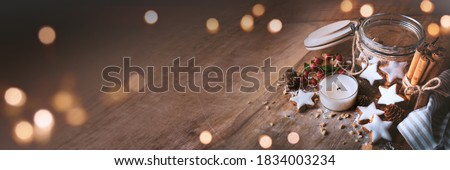 Photo of  Christmas decoration with cinnamon stars, baking ingredients. and candlelight on wood. Horizontal background with atmospheric bokeh for christmas dekoration and space for text.