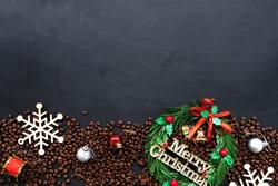 christmas decoration with coffee beans on black wooden background. flat lay. copy space for text.