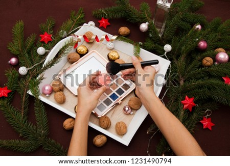 Christmas decoration with fir-tree branches, Christmas-tree balls, candies in gold packaging and nuts. Eyeshadow palette. Make up on Sylvester. Powder on the brush. #1231490794