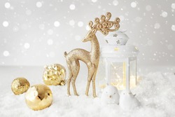 christmas decoration with lantern, reindeer snow and ornaments. snow in the background