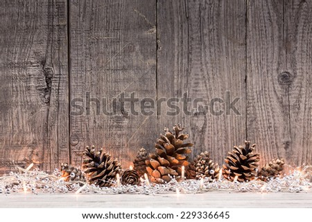 Christmas decoration with lighs and fir cones with natural wooden background
