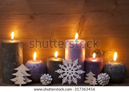 Photo of Christmas Decoration With Light Purple And Black Candles, Christmas Tree, Fir Cone, Snowflake. Peaceful Atmosphere With Candlelight. Wooden Background For Copy Space. Vintage Rustic Style