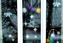 Christmas decoration with paper on the Windows with handcrafted ornaments. Christmas decoration on the Windows. Christmas decoration on the Windows is made of paper