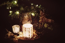 Christmas decoration with pine branches, reindeer and candlelight against a dark background in a subtle retro look