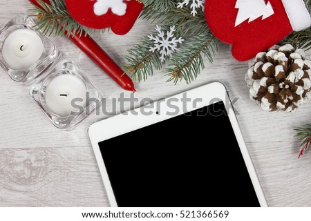 Christmas decoration with red candle, red gloves, branch of pine and pine cone on white wood background with tablet mini