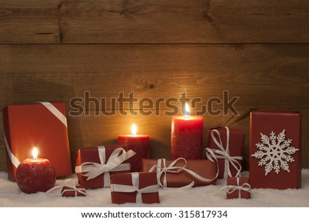 Christmas Decoration With Red Candles, Handmade Christmas Gifts, Presents,Snowflake, Snow. Peaceful Atmosphere With Candlelight For Gift Giving. Wooden Background For Copy Space. Vintage Rustic Style