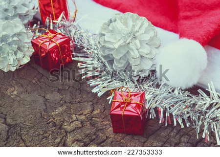 Christmas decoration with red Claus hats, silver ornament, gift box on wooden background