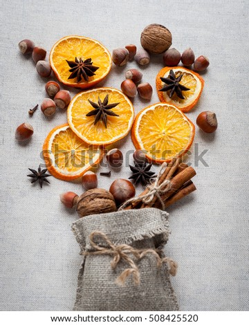 Christmas decoration with ,star anise,cinnamon stick,nuts and slices of dried oranges. top view