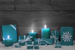 Christmas Decoration With Turquoise Candles, Handmade Christmas Gifts, Presents, Snowflake, Snow.Peaceful Atmosphere With Candlelight. Wooden,Vintage,Rustic Background.Copy Space.Black And White Image