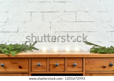 Christmas decoration with twigs of spruce on an old shelf on the background of a white brick wall
