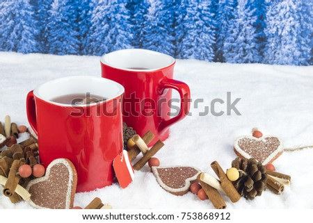 Christmas decoration with two red cups of hot tea on a background with white snow and blue pine tree landscape.