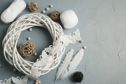 Christmas decoration with wicker ring, laces, white feathers on concrete background. Wedding, xmas rough texture flat lay