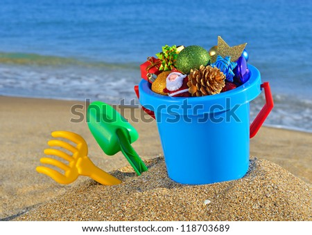 Christmas decorations and children's toys on the beach against a blue ocean