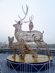 Christmas decorations around London. A display depicting three animals: a wolf, a deer, and a bird.