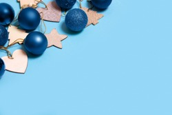 Christmas decorations, blue balls, wooden hearts, stars and Christmas trees on a blue background, close-up